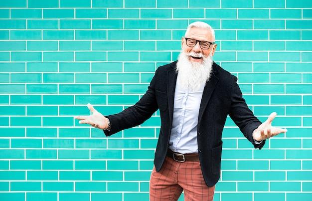 ターコイズブルーの壁を背景にポーズ歓迎気分で流行に敏感な男 Premium写真