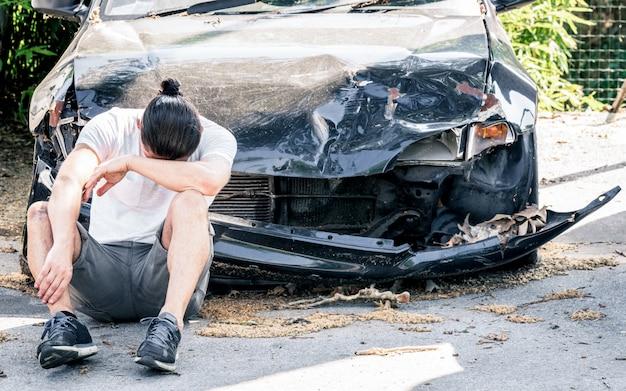 Отчаянный человек плачет на старой поврежденной машине после аварии Premium Фотографии