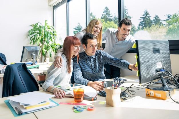 都市の代替オフィスのコンピューターを持つ若者従業員労働者のグループ Premium写真