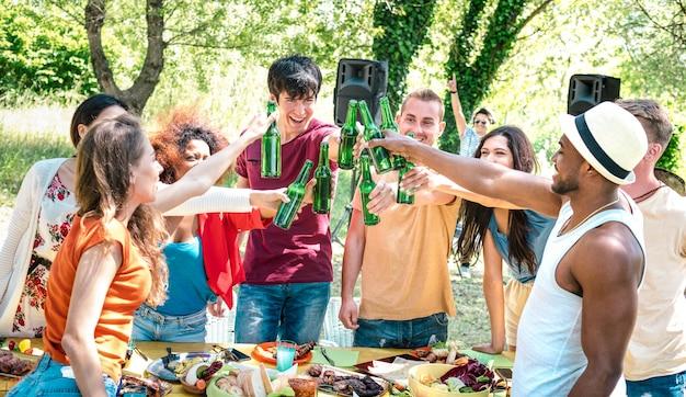 Счастливые многорасовые друзья тостов пива на вечеринке в саду барбекю Premium Фотографии
