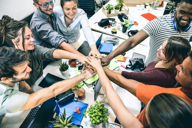 Молодые работники стартапа работника укладывают руки в студии на мозговой штурм проекта предпринимательства Premium Фотографии