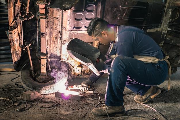 Рабочий механика молодого человека ремонтируя старый винтажный кузов автомобиля в грязном гараже Premium Фотографии