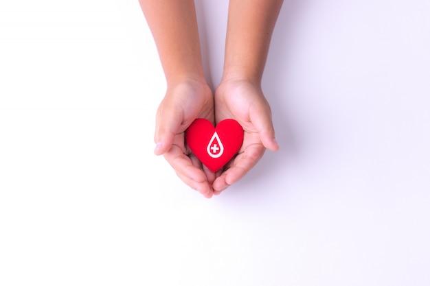 Ребенок руки держит красное сердце для сдачи крови Premium Фотографии