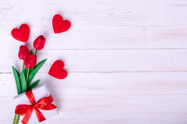 女性の日、母の日、バレンタインデーのコンセプト赤いチューリップのブーケとギフト Premium写真