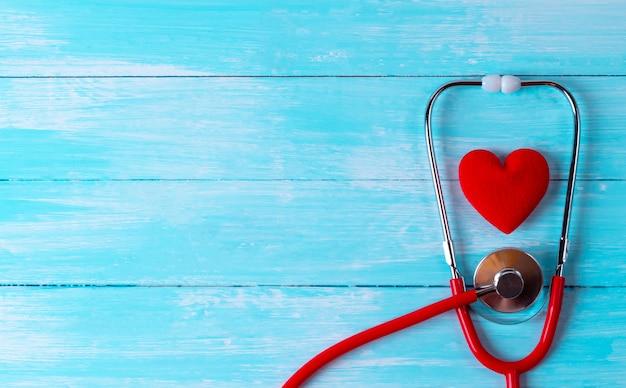 世界保健デー、ヘルスケアおよび医療の概念聴診器は青い木製の背景に赤いハートの周りにラップしました。健康保険。 Premium写真