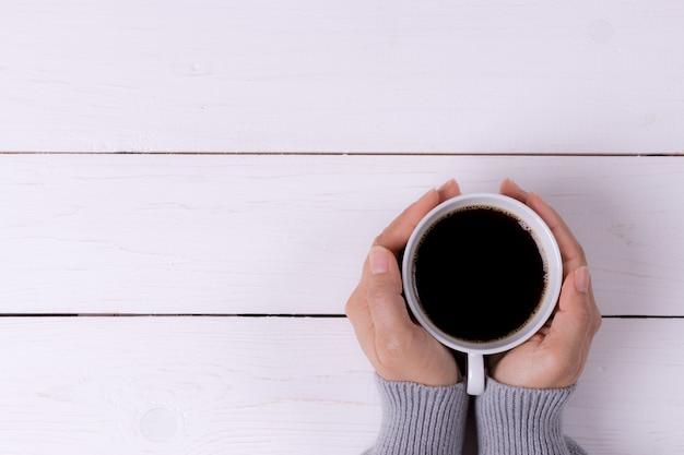 白い木製のテーブルの上の女性の手で一杯のコーヒー Premium写真