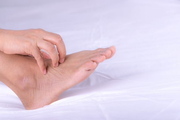 発疹や丘疹を持つ女性および彼女の足にアレルギーからの引っかき傷、健康アレルギーのスキンケアの問題。 Premium写真