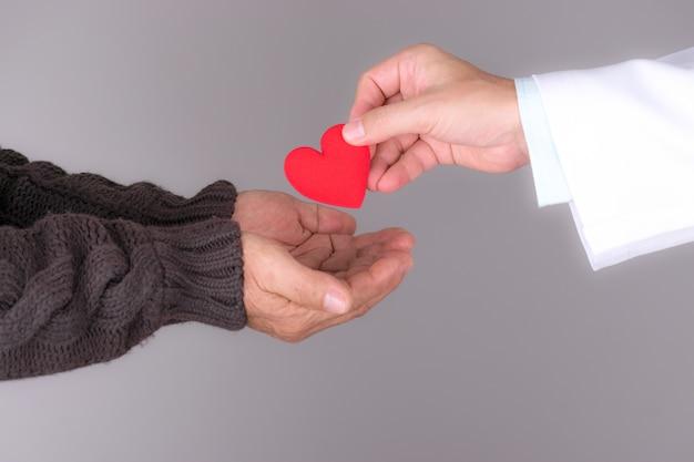 高齢患者に赤いハートを与える医師。世界の心の日。 Premium写真