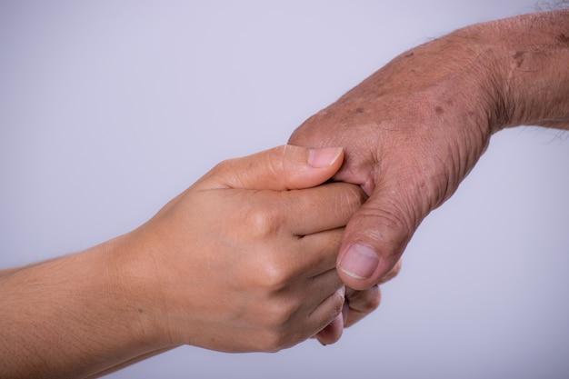 Молодая женщина держит руку своего деда Premium Фотографии