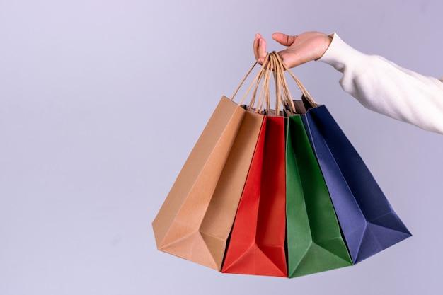 コピースペースを持つ紙袋を持つ女性の手。ブラックフライデーまたはサイバーマンデーのコンセプト。 Premium写真