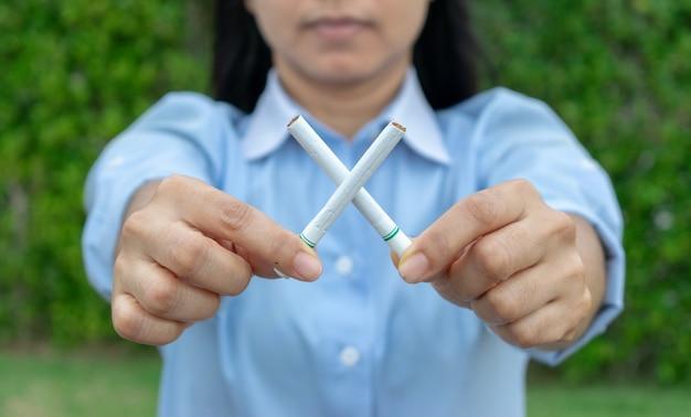 世界のたばこの日はありません。禁煙します。組んだタバコを持つ女性の手を閉じます。 Premium写真