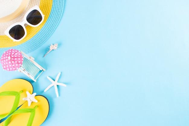 Лето или отпуск. пляжная шляпа, солнцезащитные очки, солярий, шлепанцы на голубом фоне. копировать пространство Premium Фотографии