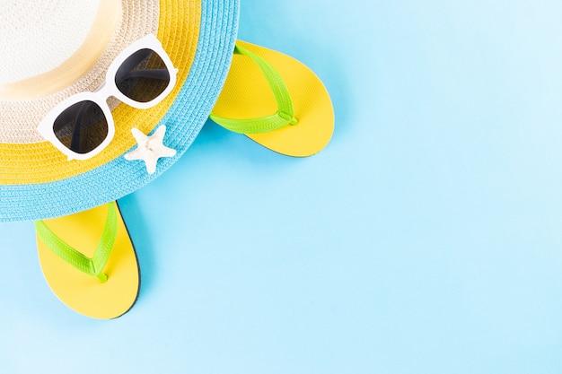 Лето или отпуск концепции. пляжная шляпа, солнцезащитные очки и флип-флоп на светло-синем фоне. копировать пространство Premium Фотографии