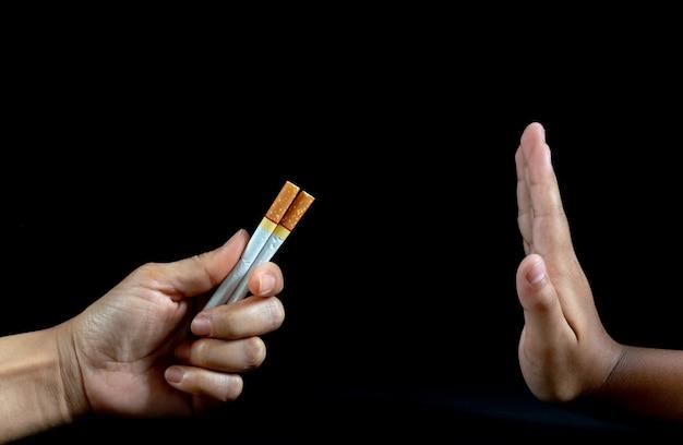 男の手を閉じる黒の背景にタバコの提供を拒否します。 Premium写真