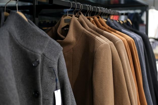 Одежда на вешалке осеннего или зимнего пальто в магазине мужской одежды. время сезона распродаж и скидок. Premium Фотографии