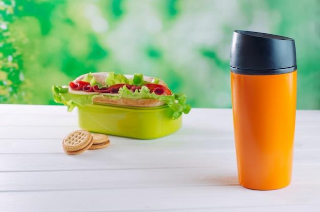 白い木製のテーブルの上のお弁当箱の近くの魔法瓶マグカップ Premium写真