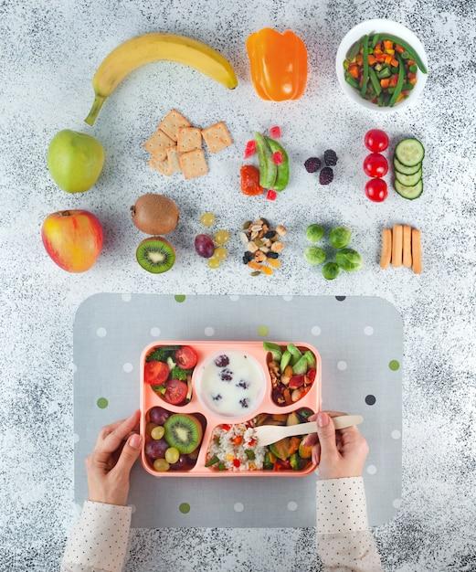 灰色の背景に食材の近くのランチボックスから昼食を食べる女 Premium写真