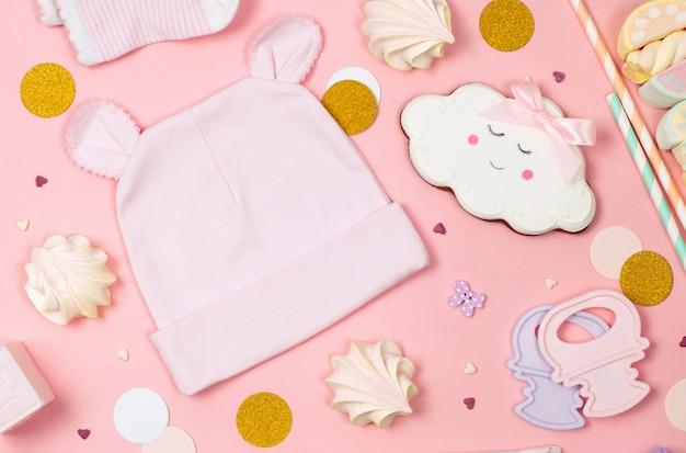 Сладости, детская одежда и аксессуары на розовом фоне Premium Фотографии