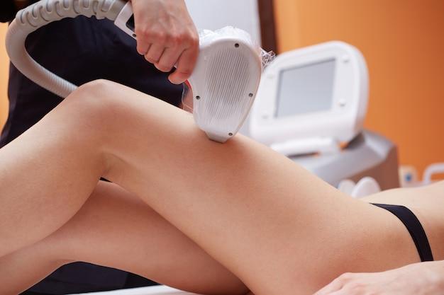 レーザーで若い女性の髪を削除する美容師 Premium写真