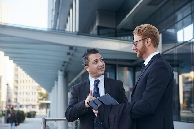 オフィスビルの外で働くビジネスマン Premium写真