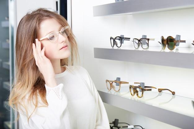 きれいな女性が新しい眼鏡を買う Premium写真