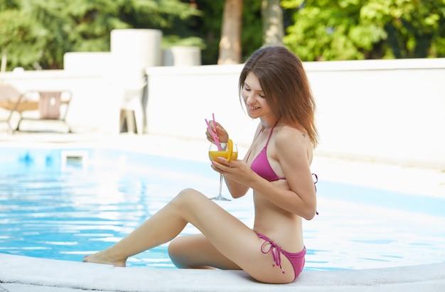 リラックスしてスイミングプールでカクテルを飲む女性 Premium写真
