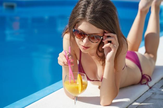 リラックスして、スイミングプールでカクテルを飲む女性 Premium写真