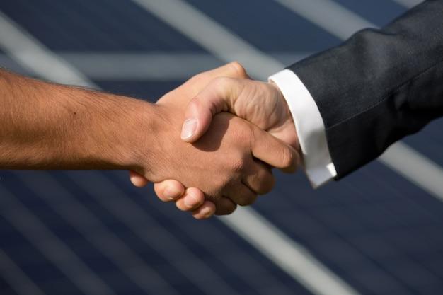 Согласие рукопожатие, солнечные панели на фоне. Premium Фотографии