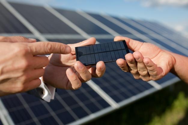 Солнечная энергия, две руки держат фотоэлектрический элемент. Premium Фотографии
