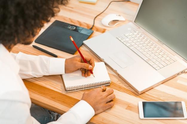 Сочинительство молодого человека в месте работы блокнота дома. арабский парень работает на деревянный стол с ноутбуком, цифровой планшет и смартфон на нем. Premium Фотографии
