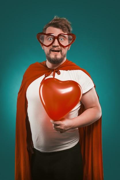 スーパーヒーローの衣装とハート型のメガネを着た正男 Premium写真