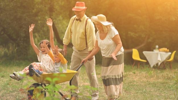 おばあちゃんとおじいちゃんは手押し車で孫を押しています Premium写真