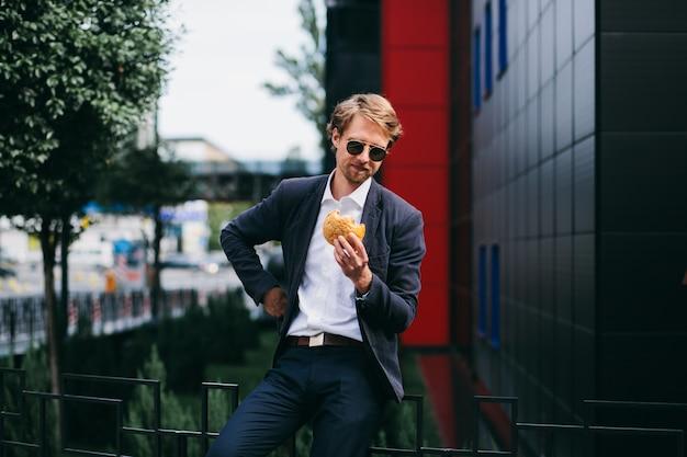 男性のオフィスワーカーは夏に外に座って、ハンバーガーを食べる Premium写真
