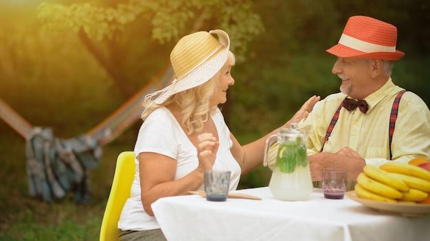 老夫婦の幸せな関係。笑顔の小さな祖父母がテーブルに座って、若者の思い出について話している。庭でフルーツとレモネードを飲む Premium写真