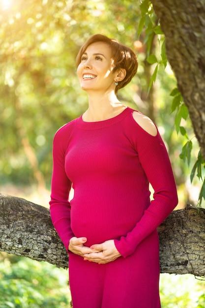 Красота беременной женщины смеется от счастья и поддерживает ее животик Premium Фотографии