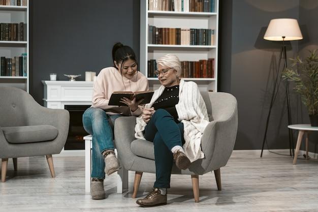 若い女性は高齢の母親のために本を読む Premium写真