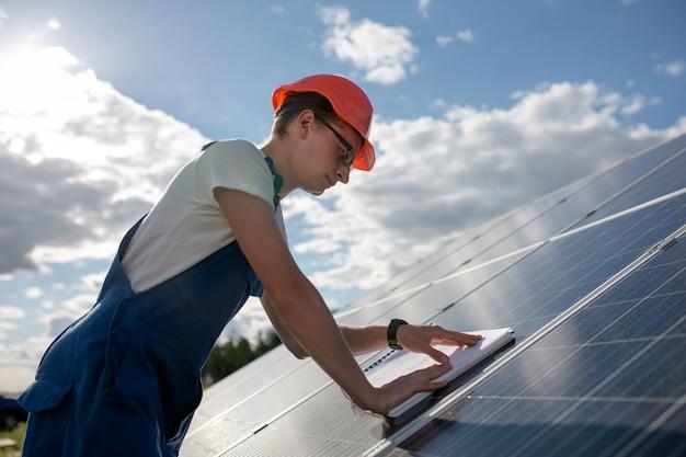 Вид сбоку на рабочий и солнечные панели. Premium Фотографии