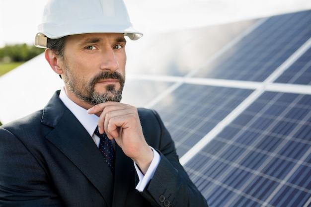 Портрет клиента в белом шлеме на солнечной электростанции. Premium Фотографии
