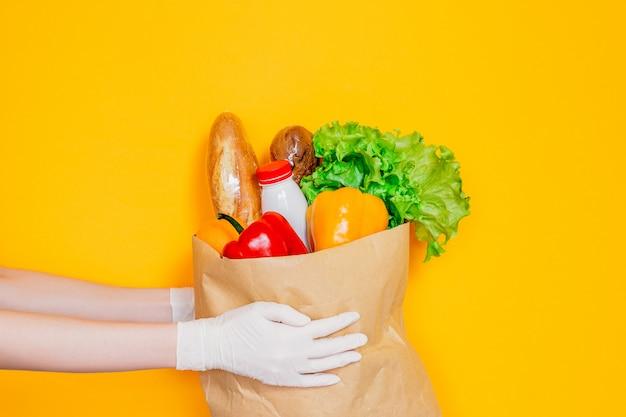 医療用手袋の女性の手は、食品、野菜、コショウ、バゲット、ヨーグルト、黄色の壁で隔離された新鮮なハーブ、検疫、コロナウイルス、安全なエコフードショッピングの配達で紙袋を保持しています。 Premium写真
