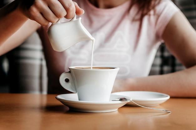 Утренний кофе. крупный план рук женщин с кофейной чашкой в кафе. женские руки держат чашки кофе на деревянном столе в кафе, старинный цветовой тон Premium Фотографии