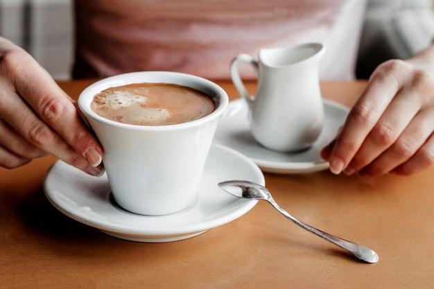 モーニング・コーヒー。カフェでコーヒーカップを持つ女性の手のクローズアップ。 Premium写真