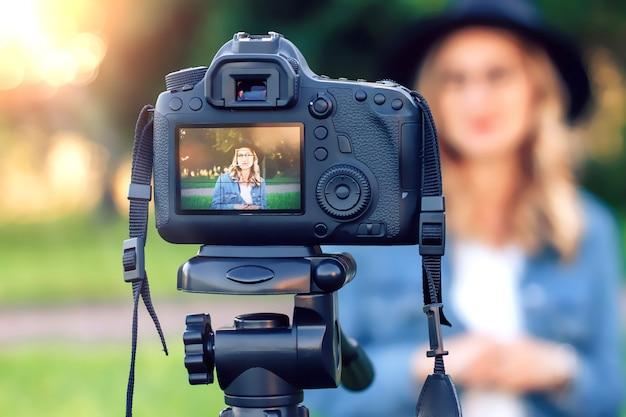 カメラの前で芝生の上に座っているスタイリッシュな若い女の子ブロガーとビデオを撮影 Premium写真