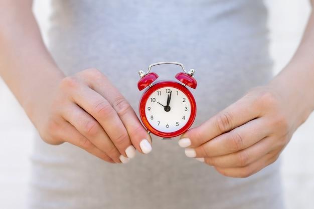 妊娠中の女性は彼女の手に赤い目覚まし時計で白いレンガの壁に立っています。妊娠、目覚まし時計と誕生時間の概念をクローズアップ Premium写真
