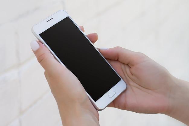 白いレンガ壁の背景、コピースペースを持つモックアップにスマートフォンを持つ女性の手 Premium写真