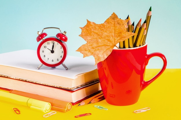 青色の背景に赤い目覚まし時計、色鉛筆、書籍、カエデの葉。 Premium写真