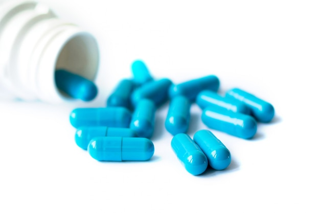 青いカプセル、コピースペースと白い背景で隔離の丸薬。白い瓶にカプセル。 Premium写真
