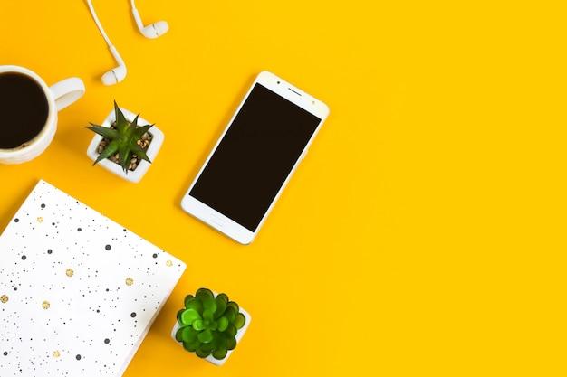 Утренний кофе, блокнот, мобильный телефон, растения на желтом Premium Фотографии