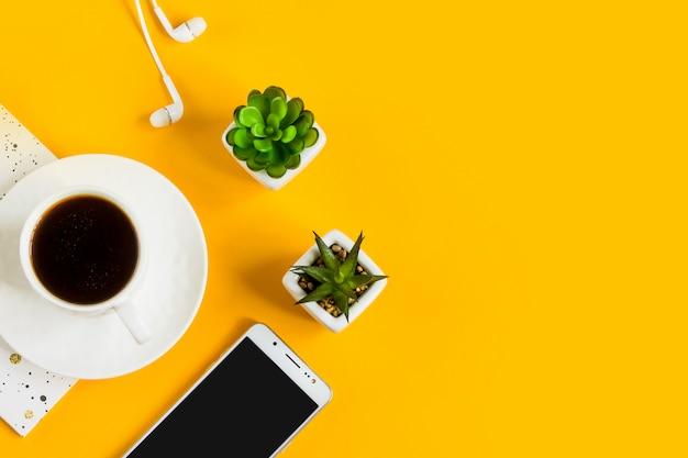 朝のコーヒー、ノート、携帯電話、黄色の背景の植物。ビジネス黄色の背景。 Premium写真
