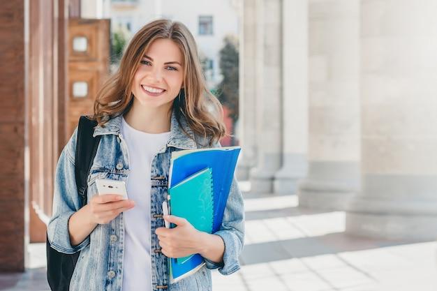 Студент маленькой девочки усмехаясь против университета. Premium Фотографии