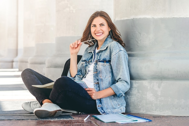 女子学生が大学の近くに座って、笑顔します。かわいい女子学生は、フォルダー、ノートブック、笑いを保持しています。女の子がレッスンを教える Premium写真
